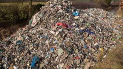 Mountain of steaming waste including dirty nappies fly-tipping on quiet country lane