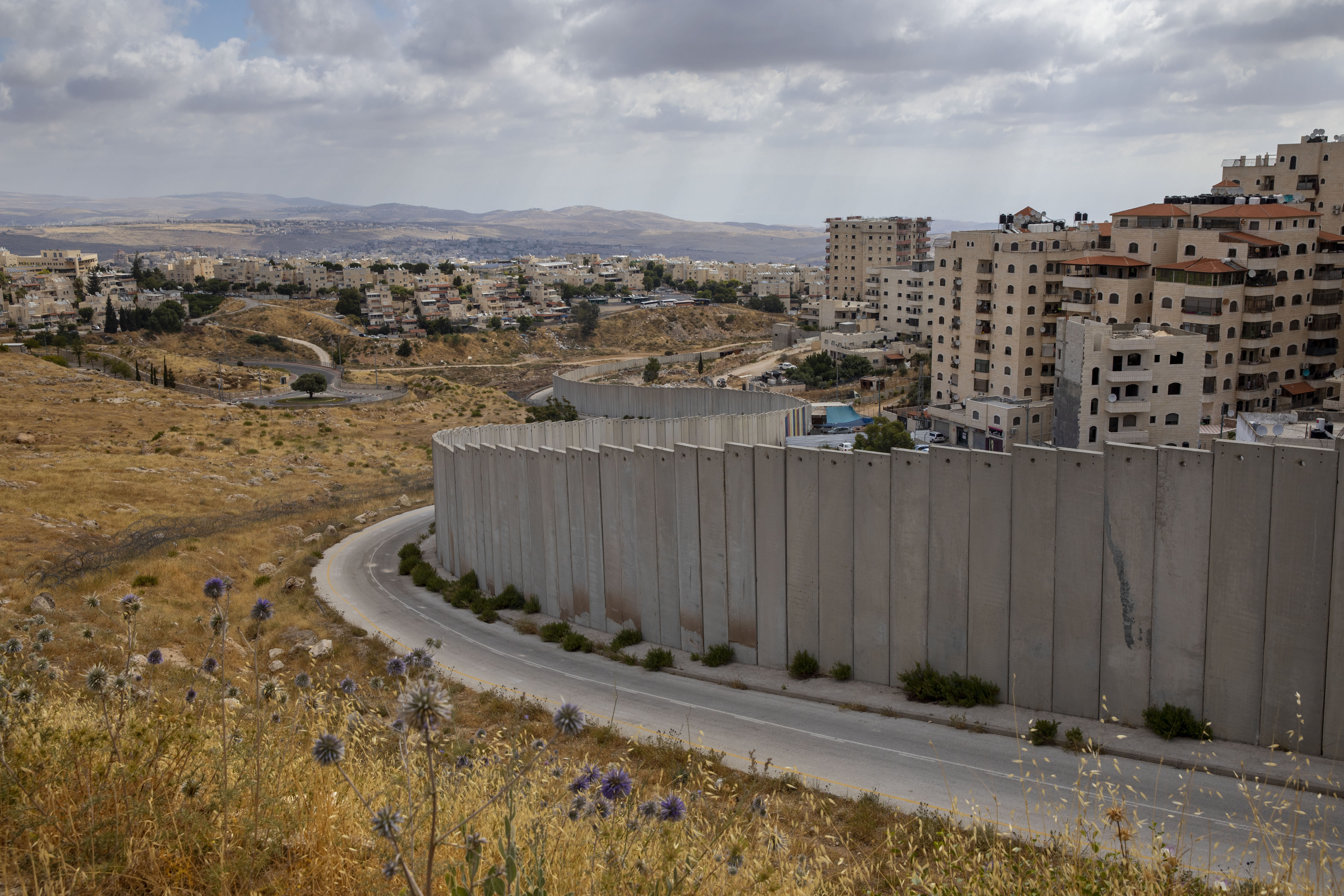 FILE - In this June 19, 2020, file photo, the Shuafat refugee camp is seen behind a section of Israel's separation barrier in Jerusalem. Peter Beinart, an influential American commentator, has shocked the Jewish establishment and Washington policy-making circles by breaking a long-standing taboo: He has endorsed the idea of a democratic entity of Jews and Palestinians living with equal rights between the Jordan River and the Mediterranean. (AP Photo/Oded Balilty, File)