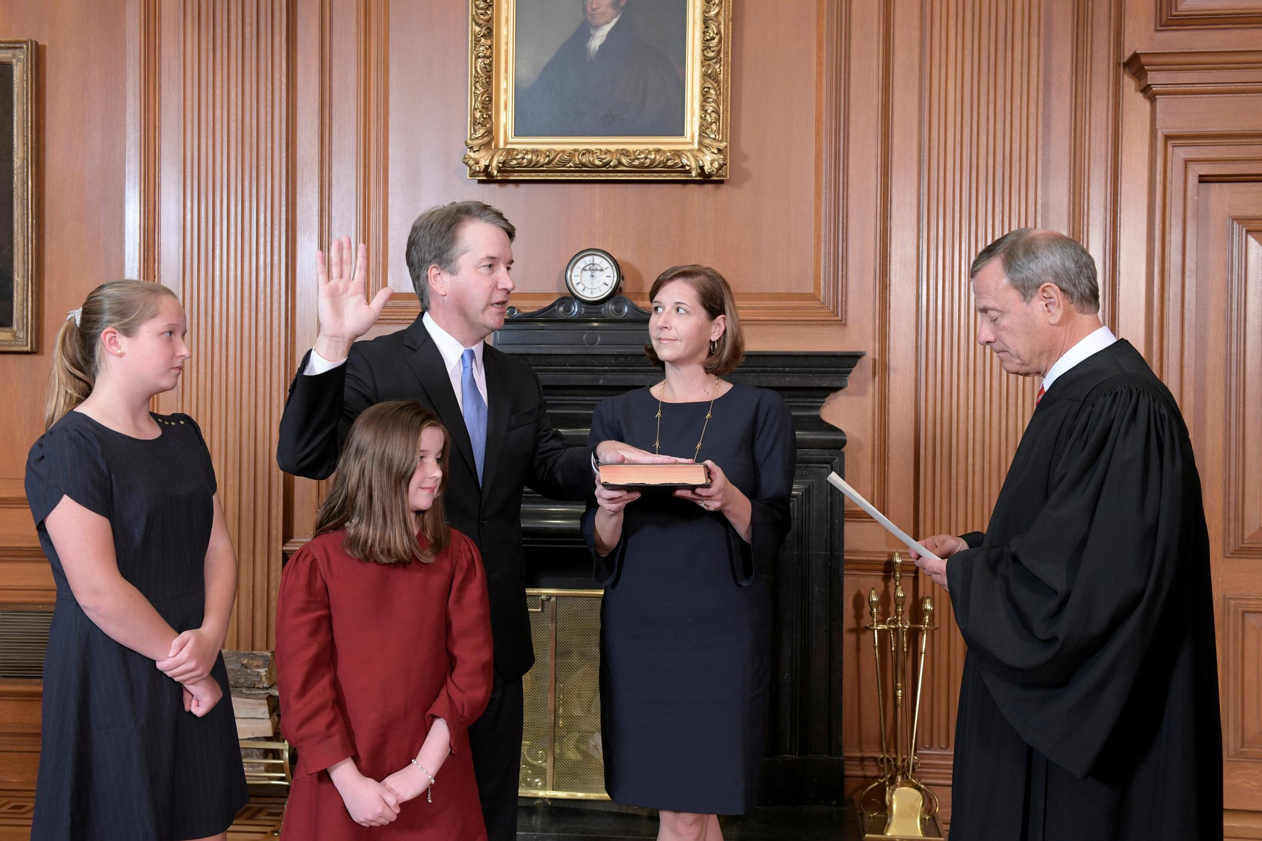 Judge Brett Kavanaugh is sworn in as an Associate Justice of the U.S. Supreme Court by Chief Justice John Roberts as Kavanaugh's wife Ashley holds the family bible and his daughters Liza and Margaret look on in a handout photo provided by the U.S. Supreme Court taken at the Supreme Court building in Washington, U.S., October 6, 2018. Fred Schilling/Collection of the Supreme Court of the United States/Handout via Reuters ATTENTION EDITORS - THIS IMAGE WAS PROVIDED BY A THIRD PARTY. TPX IMAGES OF THE DAY