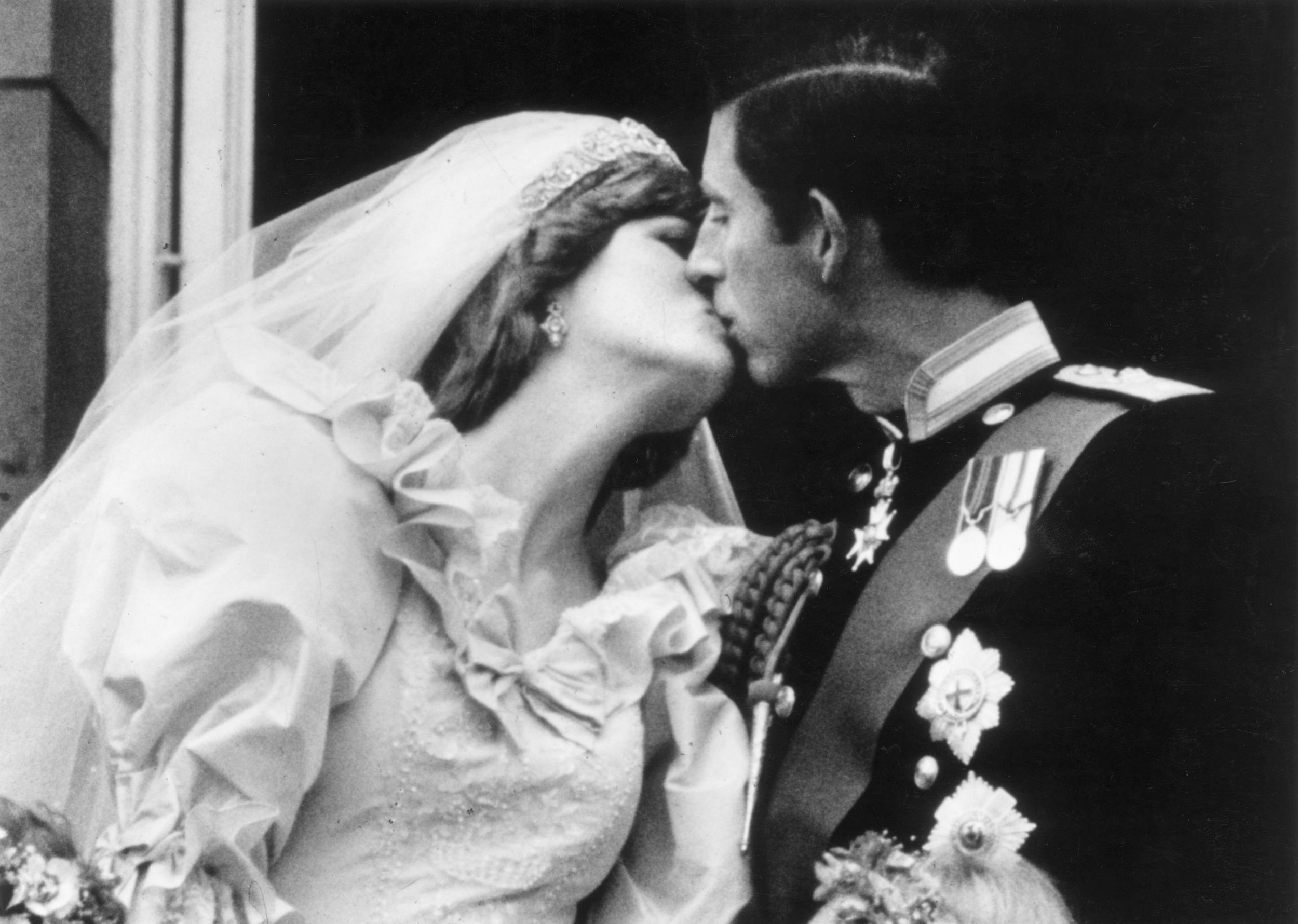 Prince Charles, the Prince of Wales kissing his wife, Princess Diana (1961 - 1997), on the balcony of Buckingham Palace after their marriage.