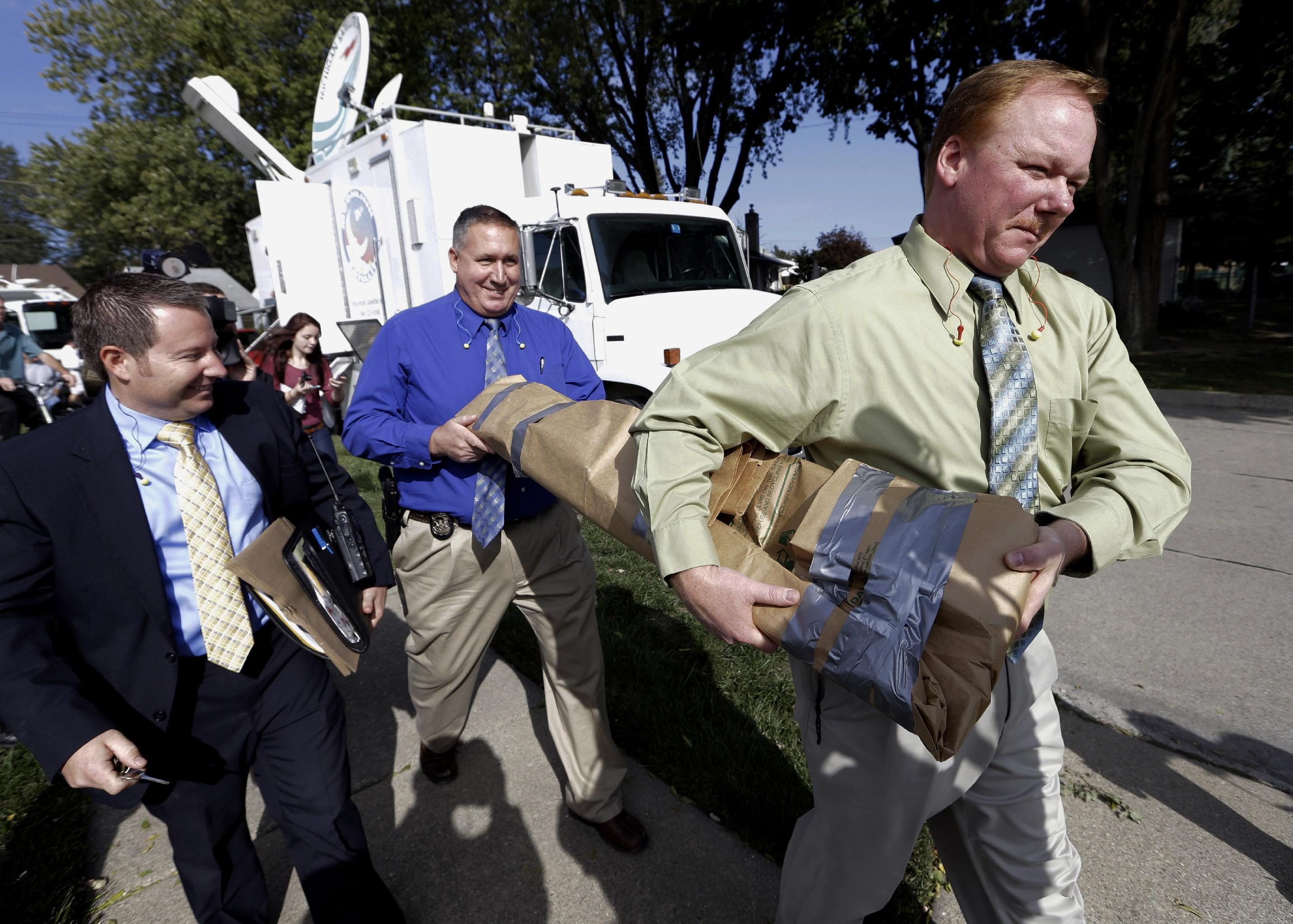 Roseville Police Department detectives carry soil samples removed from a shed floor of a Roseville, Mich., home Friday, Sept. 28, 2012. Police have been told by a source that former Teamsters boss Jimmy Hoffa may be buried beneath a driveway. (AP Photo/Paul Sancya)