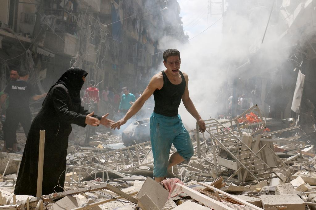 People walk amid the rubble of destroyed buildings following a reported air strike on the rebel-held neighbourhood of al-Kalasa in Aleppo, Syria on April 28, 2016