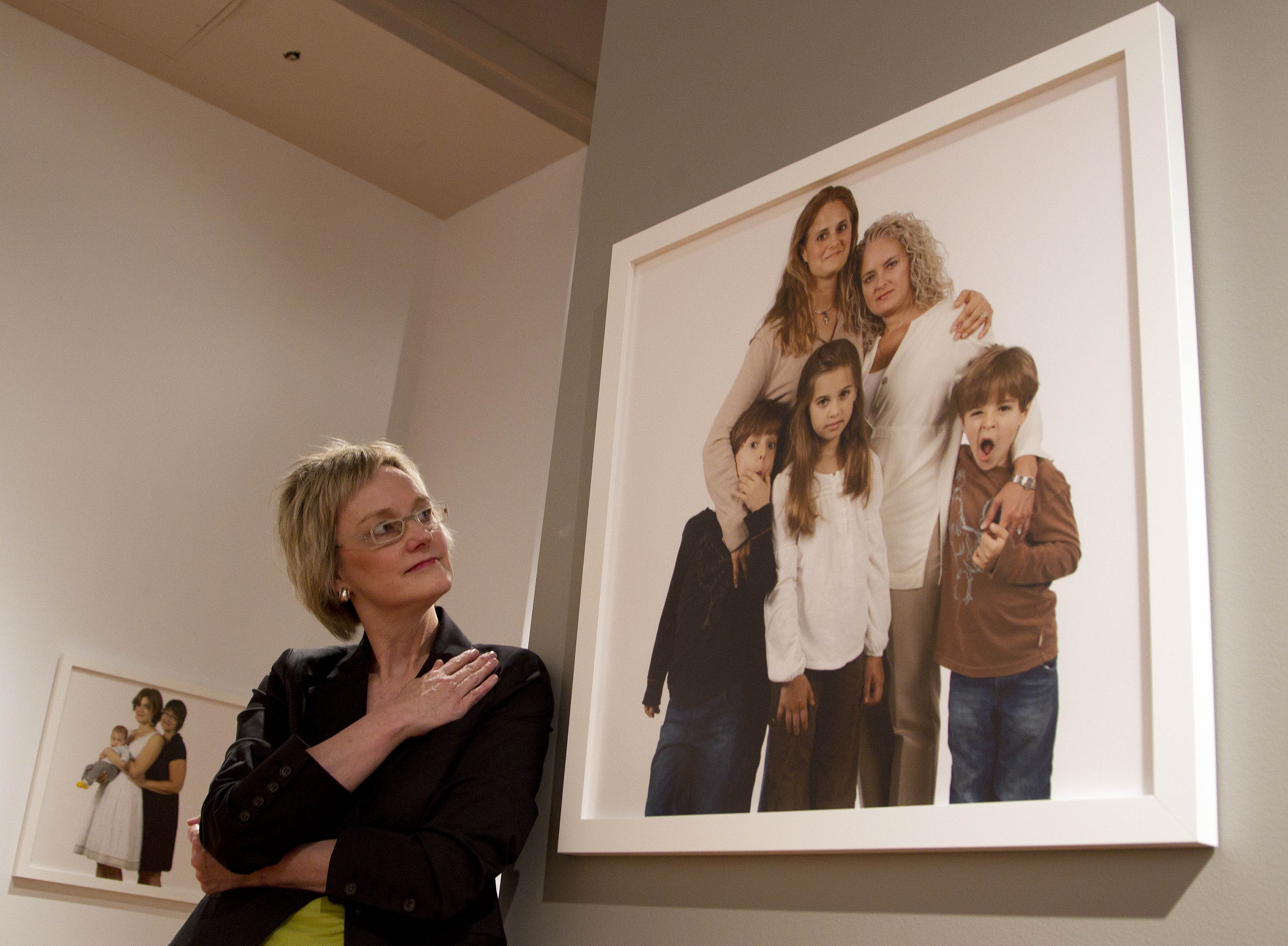 Photographer Carolyn Sherer looks at her group of photographs of lesbian families on Thursday, March 29, 2012 at the Civil Rights Institute in Birmingham, Ala.,Thursday, March 29, 2012. The photographs will be displayed thru June. Sherer says she hopes the photographs start a conversation about equality for everyone. (AP Photo/Dave Martin)