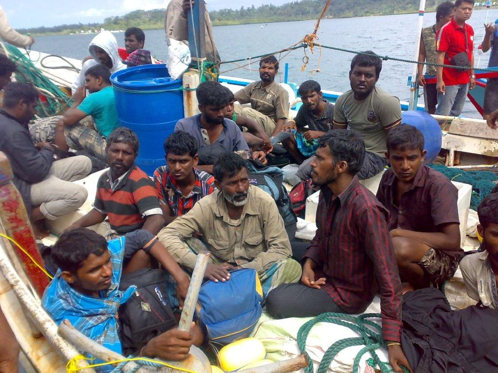Sri Lankan asylum-seekers sit on their boat in the Mentawai island group in West Sumatra, after being intercepted by Indonesian authorities, in 2012 (AFP Photo/-)