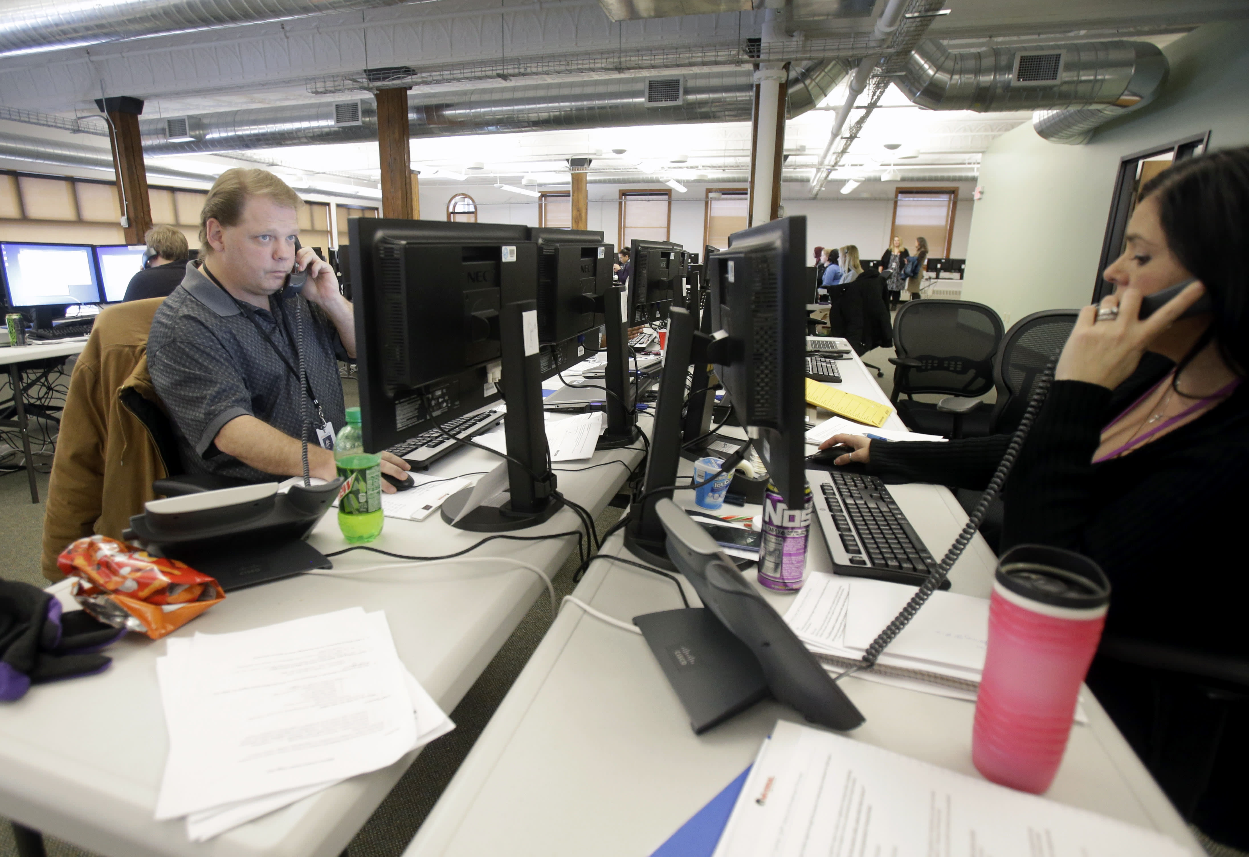 In this Dec. 31, 2013 photo, guides work the phone bank at MnSure, Minnesota's insurance marketplace in St. Paul, Minn.The 14 states running their own insurance marketplaces had their 2014 budgets footed by the federal government, but starting in 2015 were supposed to fund themselves. Most planned to do so with revenue derived from enrollments, but in states like Minnesota, the lagging pace of sign ups has thrown that into question. (AP Photo/Jim Mone)