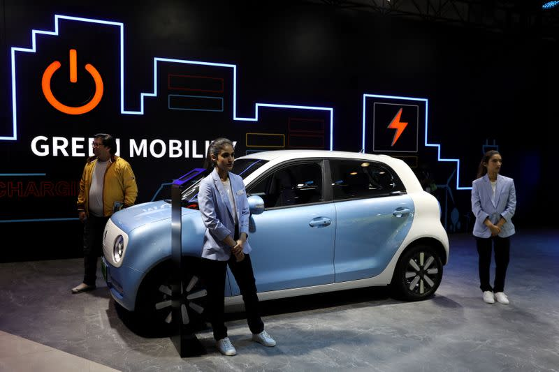 FILE PHOTO: Models pose next to Great Wall Motors (GWM) GWM R1 electric car at its pavilion at the India Auto Expo 2020 in Greater Noida