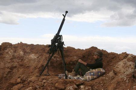 A rebel fighter sits near a weapon in Al-Lataminah village