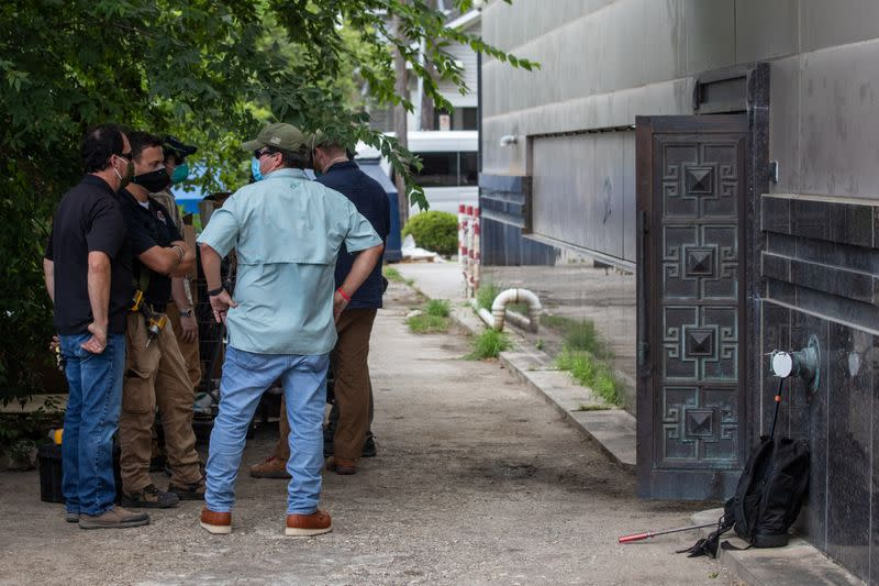 Plain clothes U.S. security officials stand outside the back door of China's Consulate after Chinese employees left the building, in Houston