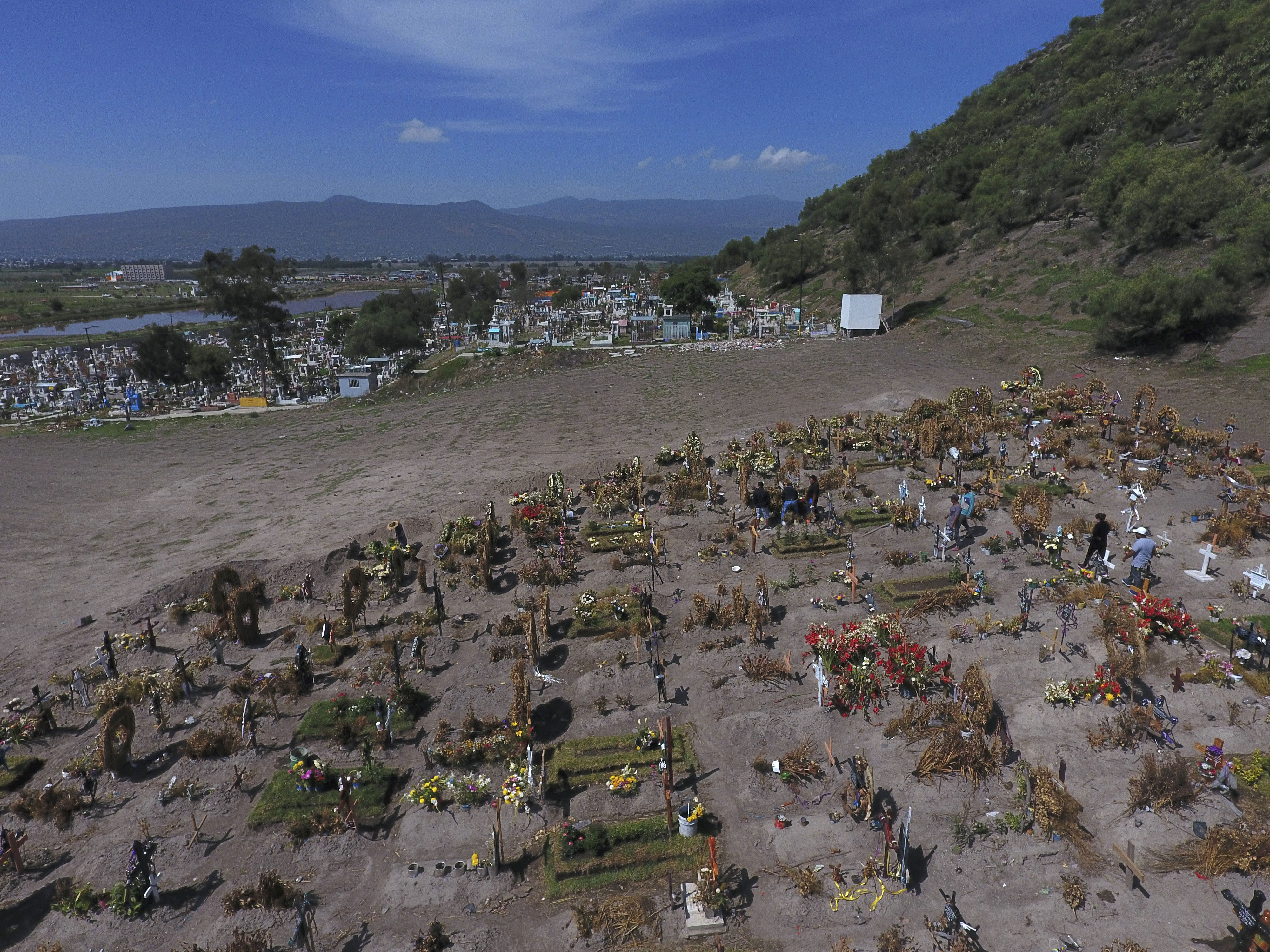 Crosses and wreaths mark graves in a section of the Municipal Cemetery of Valle de Chalco opened two months ago to accommodate the surge in deaths amid the ongoing coronavirus pandemic, on the outskirts of Mexico City, Thursday, July 2, 2020. (AP Photo/Rebecca Blackwell)