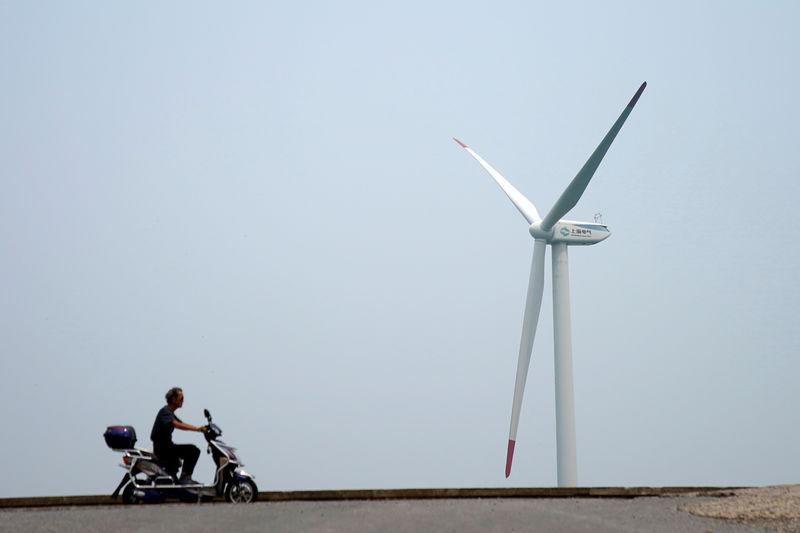 A man rides an electric scooter past a wind turbine in Shanghai