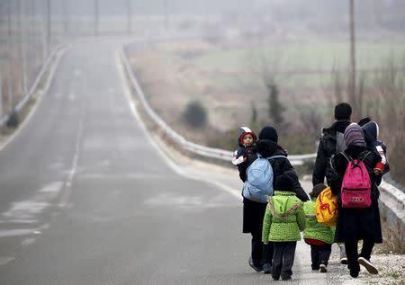 Stranded Afghan migrants make their way towards the Greek-Macedonian border near the Greek village of Idomeni