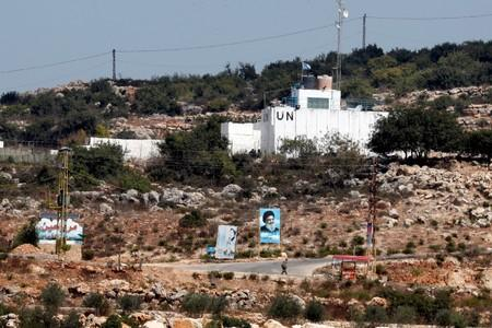 FILE PHOTO: A banner depicting Hezbollah leader Sayyed Hassan Nasrallah and an United Nation's post are seen in Lebanon from the Israeli side of the border, near Zar'it in northern Israel