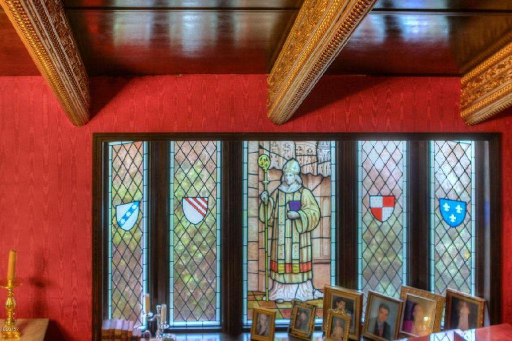 <p>The darkness of the house sets off the sunlight streaming through stained glass, Barton says.</p>