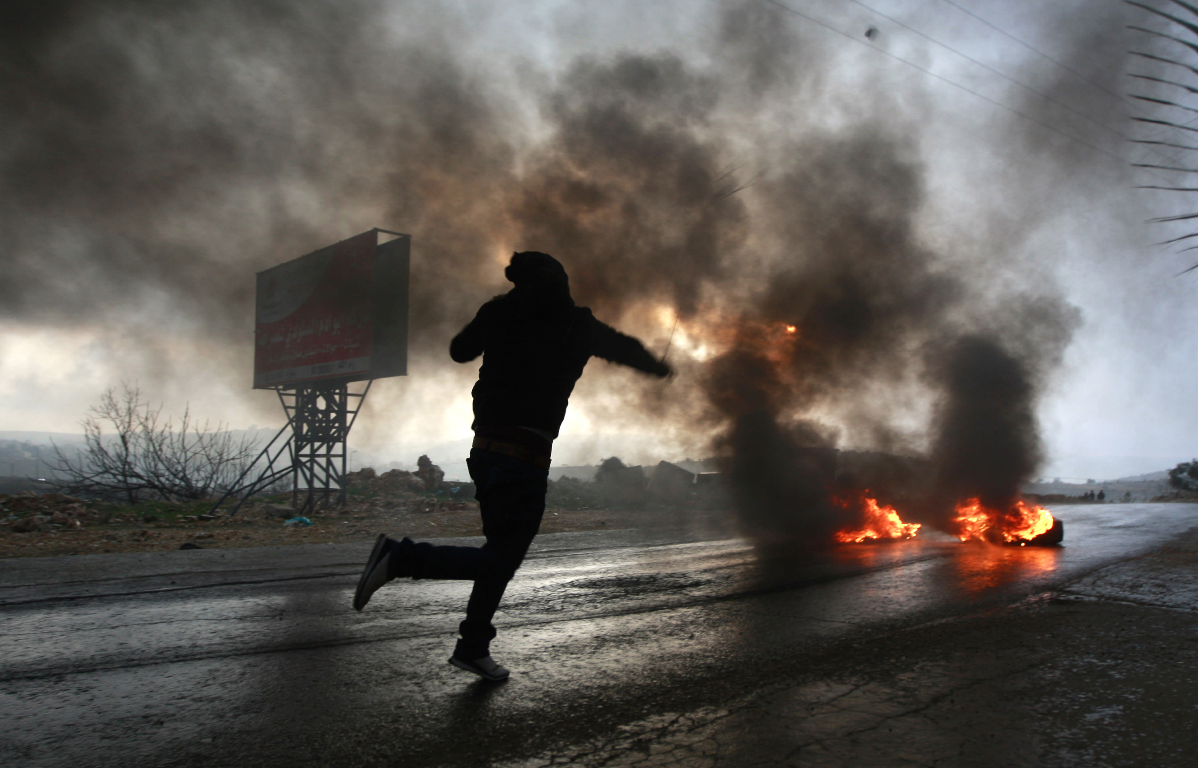 A Palestinian uses a slingshot to hurl stones at Israeli forces during clashes at a protest against the expansion of the nearby Jewish settlement Ofra outside the village of Silwad, near the West Bank city of Ramallah, Friday, Jan. 10, 2014. (AP Photo/Majdi Mohammed)