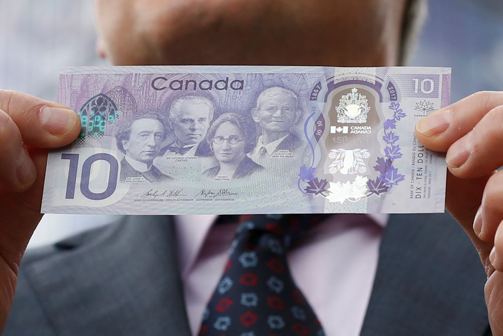 Bank of Canada Governor Stephen Poloz holds a commemorative $10 bank note celebrating the 150th anniversary of Canada's confederation during a photo opportunity in Ottawa, Ontario, Canada June 1, 2017. (Reuters)