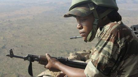 A female Cameroonian soldier stands guard at an observation post on a hill in the Mandara Mountain chain in Mabass, overlooking Nigeria, northern Cameroon
