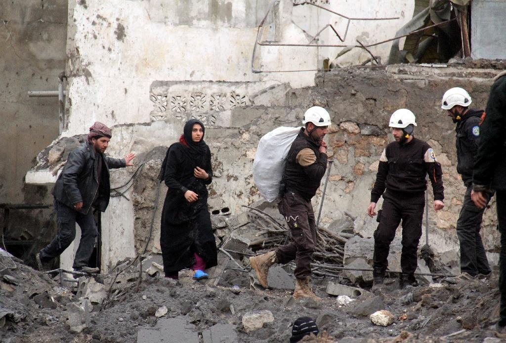 Syrian Civil Defence volunteers, also knowns as the White Helmets, help evacuate a woman and a man following a reported airstrike that targeted the Idlib bus station on January 18, 2017