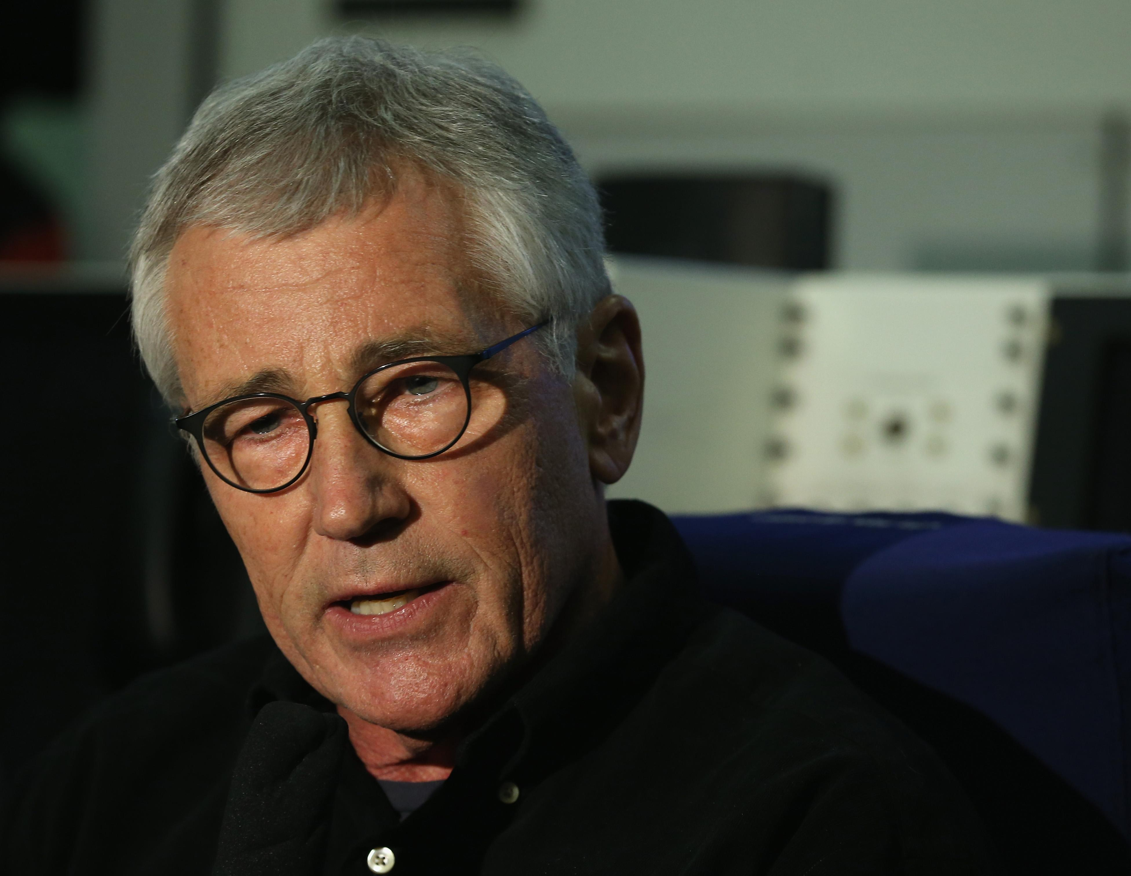 US Secretary of Defense Chuck Hagel speaks to the media about his trip to Afghanistan on board his plane on December 5, 2014 (AFP Photo/Mark Wilson)