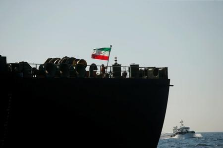 A crew member raises the Iranian flag at Iranian oil tanker Adrian Darya 1 before named as Grace 1 as it sits anchored after the Supreme Court of the British territory lifted its detention order in the Strait of Gibraltar