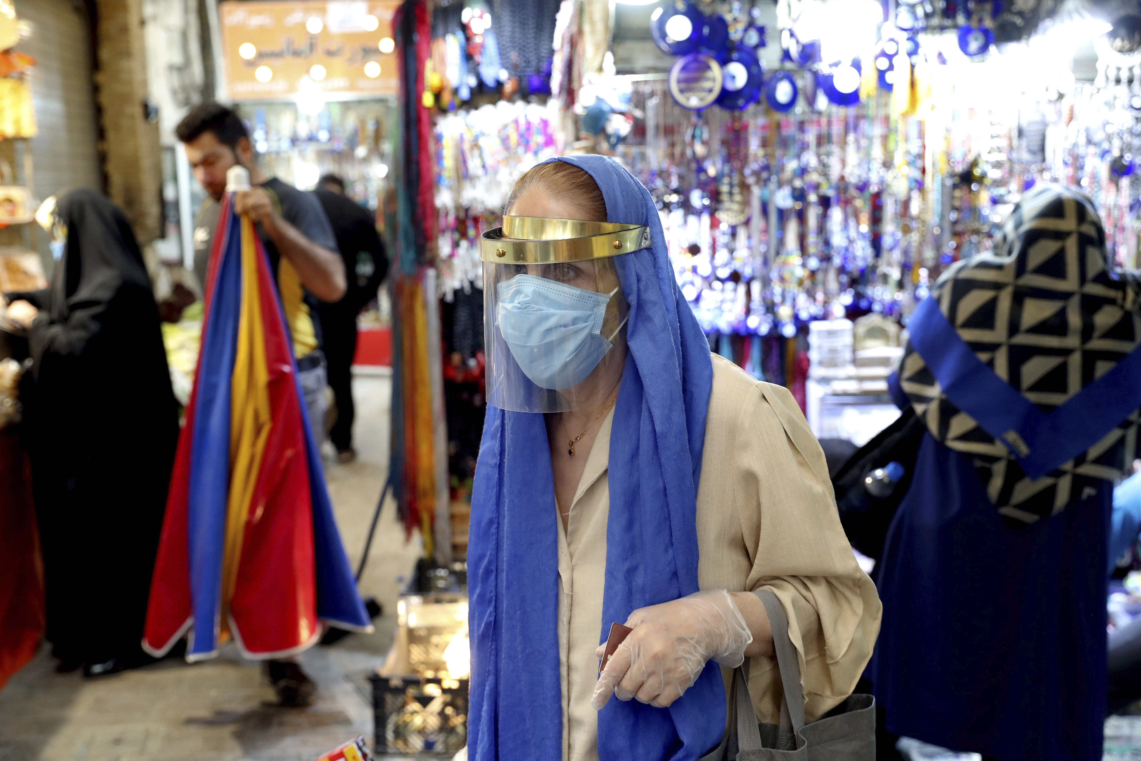 A woman wearing a protective face mask and gloves to help prevent the spread of the coronavirus walks through the Tajrish traditional bazaar in northern Tehran, Iran, Thursday, Oct. 15, 2020. Eight months after the pandemic first stormed Iran, pummeling its already weakened economy and sickening officials at the highest levels of its government, authorities appear just as helpless to prevent its spread. (AP Photo/Ebrahim Noroozi)