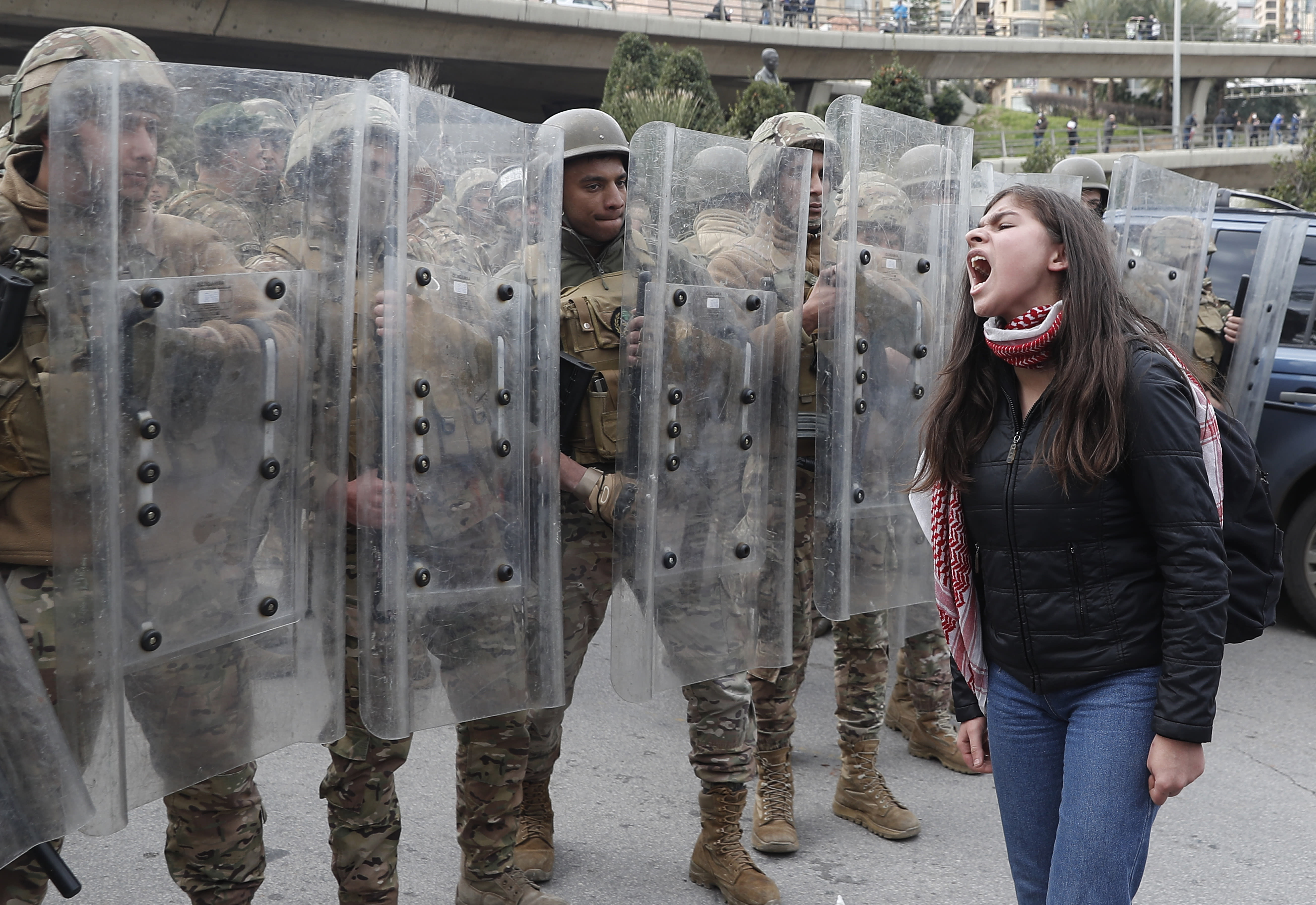 A protester shouts slogans in front of army soldiers during a protest against a parliament session vote of confidence for the new government in downtown Beirut, Lebanon, Tuesday, Feb. 11, 2020. Clashes broke out Tuesday between Lebanese protesters and security forces near the parliament building in central Beirut, where the new Cabinet is scheduled to submit its policy statement ahead of a vote of confidence. (AP Photo/Hussein Malla)