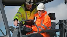 High-vis heir: William tries out a digger 'to tell George' as he meets apprentices