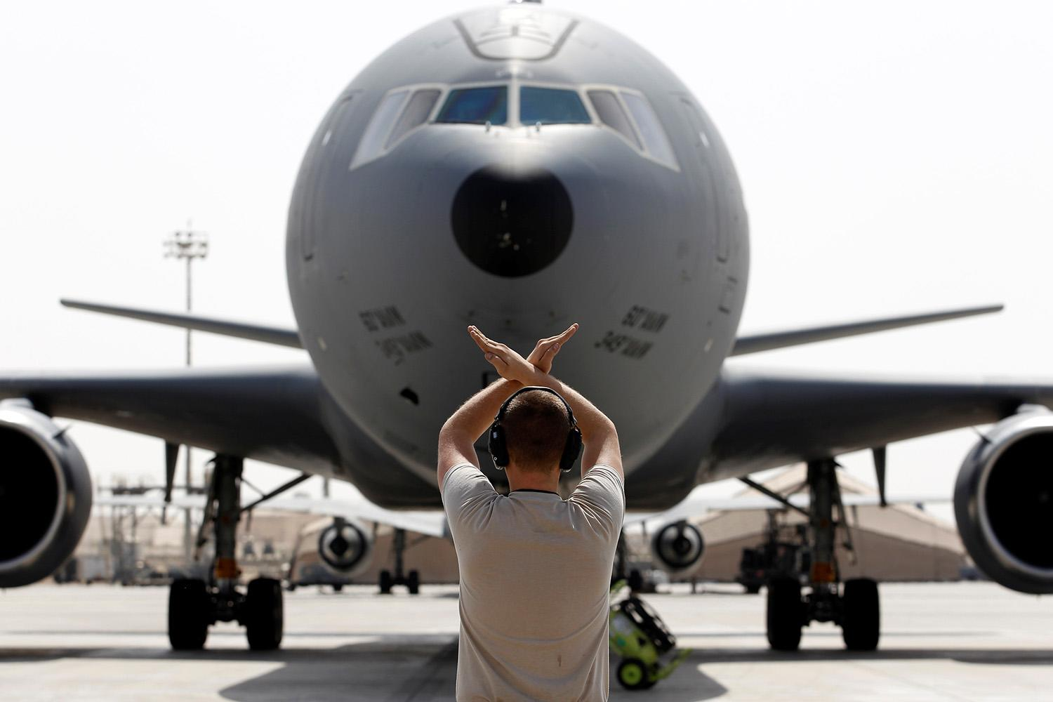 <p>A U.S .Air Force ground director guides the KC-10 Extender upon its arrival after providing mid-air refueling support to Operation Inherent Resolve over Iraq and Syria, at an Air Force Base in the Arabian Gulf, March 13, 2017. (Photo: Hamad Mohammed/Reuters) </p>