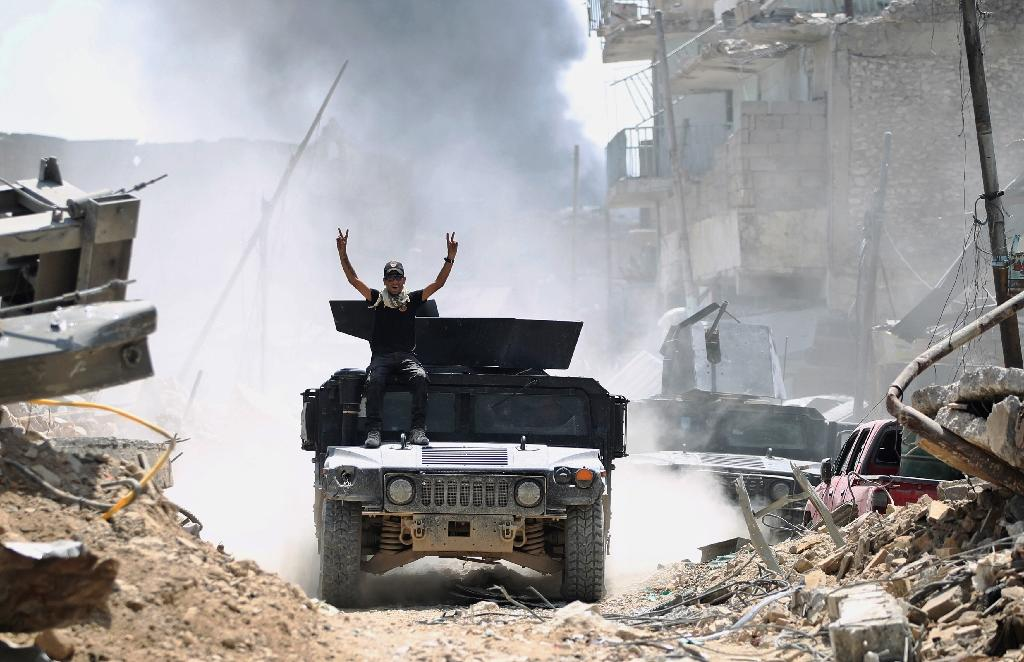 A member of Iraq's Counter-Terrorism Service flashes the victory sign from an advancing humvee in the Old City of Mosul on June 30, 2017 (AFP Photo/AHMAD AL-RUBAYE)