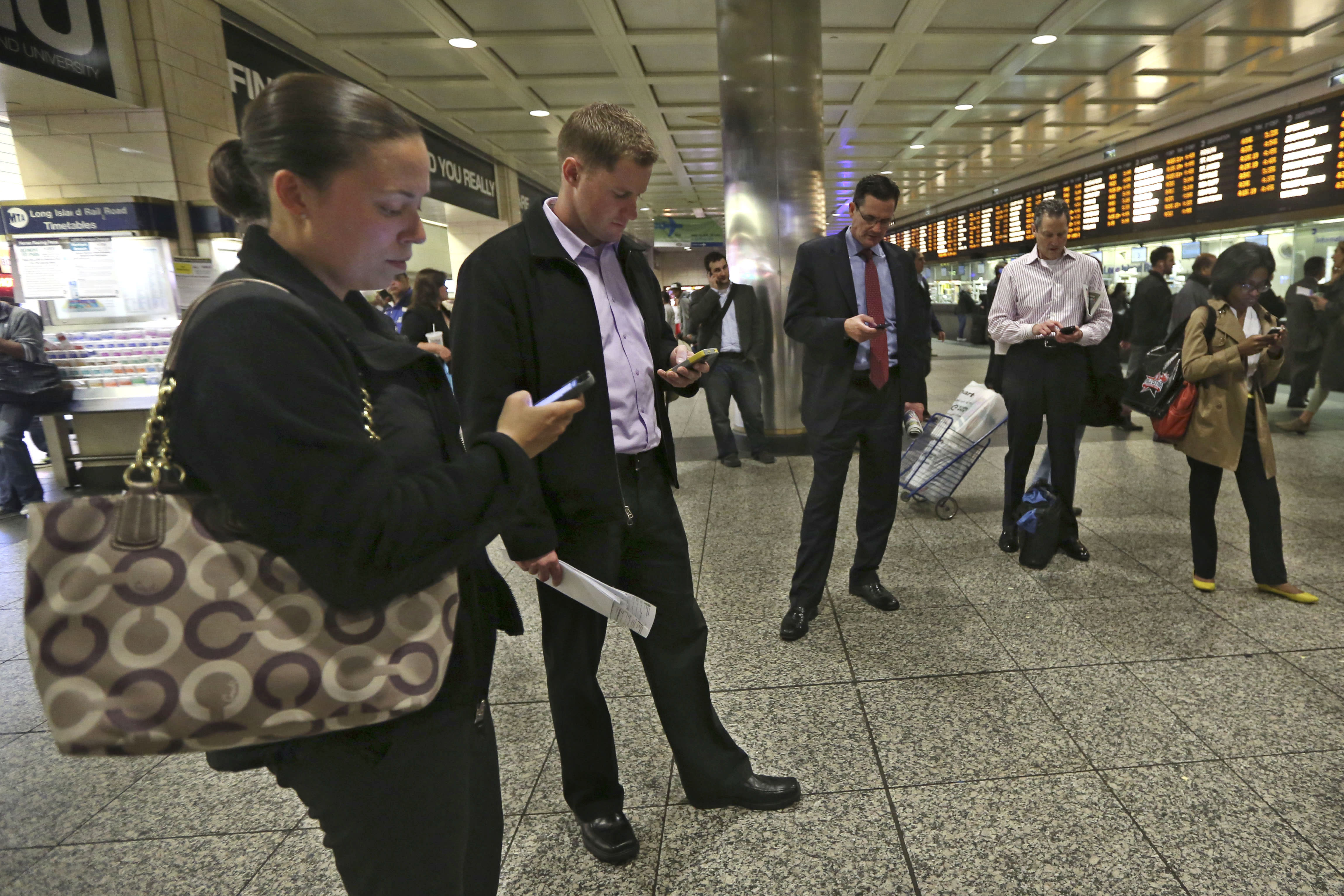 This Thursday, May 9, 2013 photo shows evening rush hour commuters looking at their smart phones while waiting for trains at the Long Island Railroad area inside Penn Station in New York. The busiest passenger train station in the United States, gateway to the biggest city in the nation, is a 1960s-era, utilitarian labyrinth built in what is essentially the basement of Madison Square Garden. Two decades after ambitious plans were unveiled to improve Penn Station while expanding it into the massive Beaux Arts post office building across the street, there are few visible signs of change. (AP Photo/Mary Altaffer)