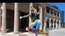 Guy Rides Longboard in Crazy Rainbow Costume