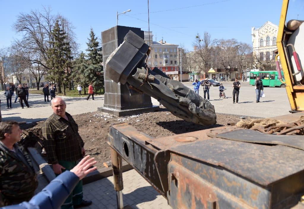 Communal workers remove the toppled Soviet-era memorial for Nikolai Rudnev in Kharkiv on April 11, 2015 (AFP Photo/Sergey Bobok)
