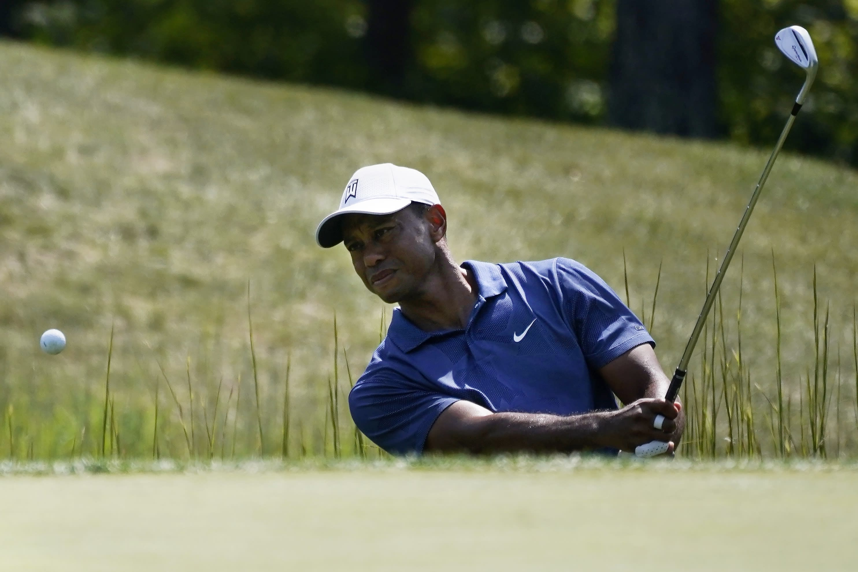 Tiger Woods makes his first attempted shot out of a trap on the fourteenth tee during the third round of the Northern Trust golf tournament at TPC Boston, Saturday, Aug. 22, 2020, in Norton, Mass. (AP Photo/Charles Krupa)