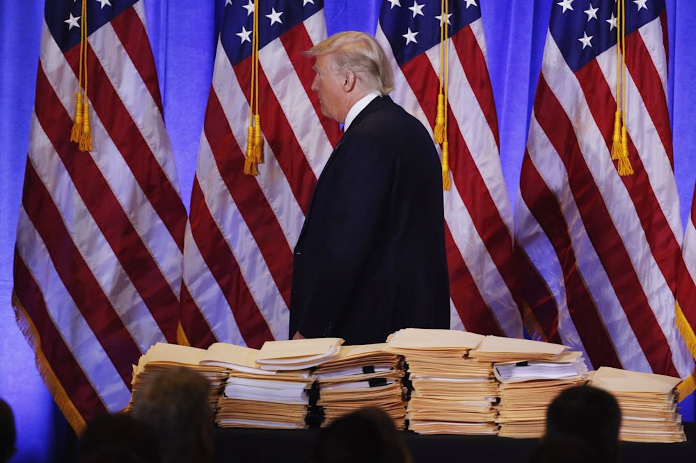 Trump walks past a pile of papers during his first news conference as president-elect. (Photos: Lucas Jackson/Reuters)