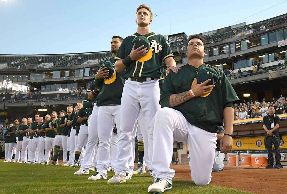 Bruce Maxwell, right, became the first MLB player to take a knee in September. (Getty Images)