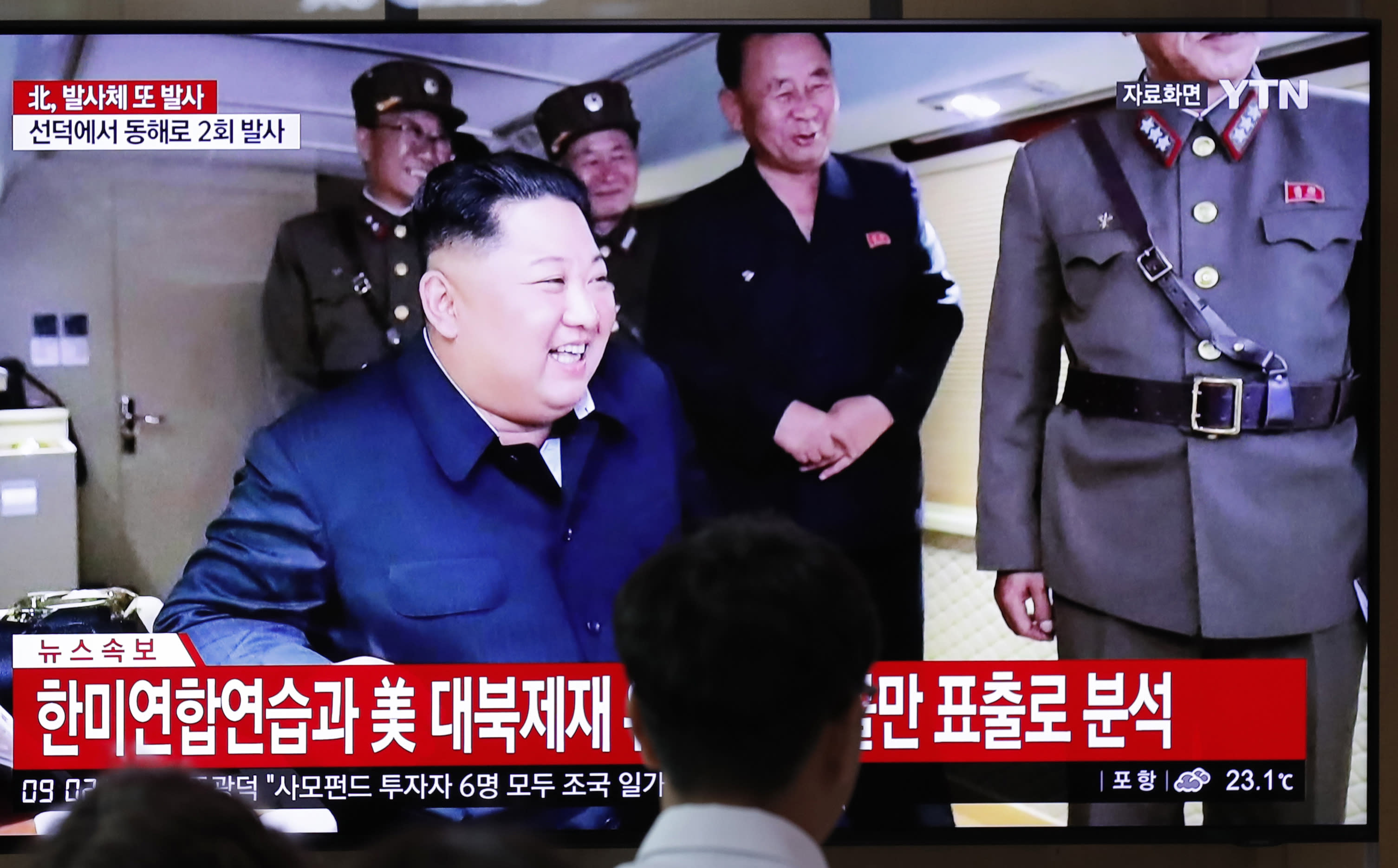 """People watch a TV news program reporting North Korea's firing of projectiles with a file image of North Korean leader Kim Jong Un at the Seoul Railway Station in Seoul, South Korea, Saturday, Aug. 24, 2019. North Korea fired two suspected short-range ballistic missiles off its east coast on Saturday in the seventh consecutive week of weapons tests, South Korea's military said, a day after it threatened to remain America's biggest threat in protest of U.S.-led sanctions on the country. The Korean letters read: """"North Korea fired projectiles."""" (AP Photo/Lee Jin-man)"""
