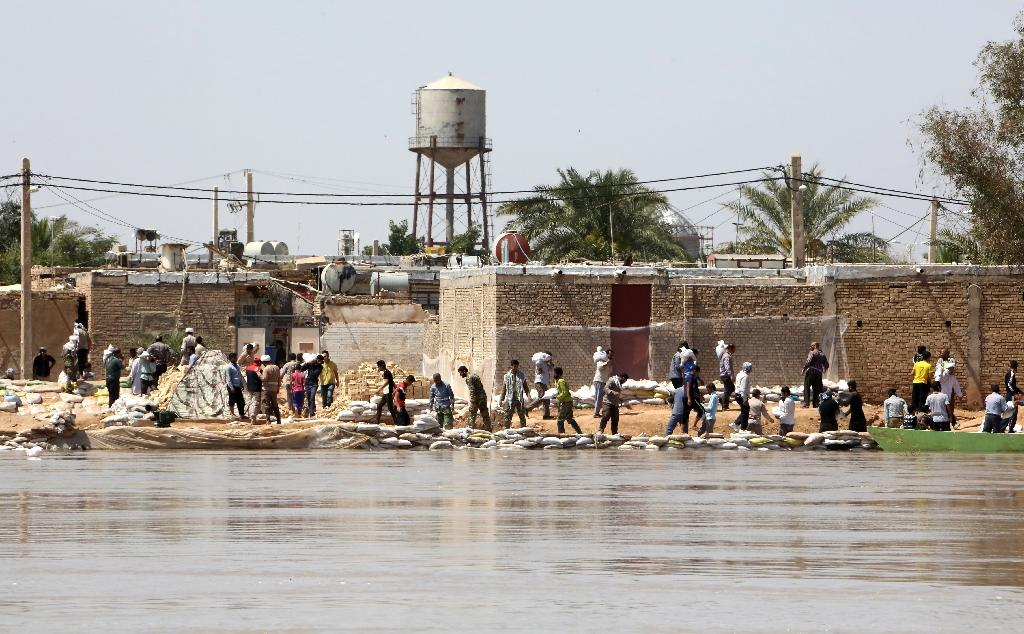 Iranians carry sandbags to build barricades against flood water in the city of Hamidiyeh, Khuzestan province