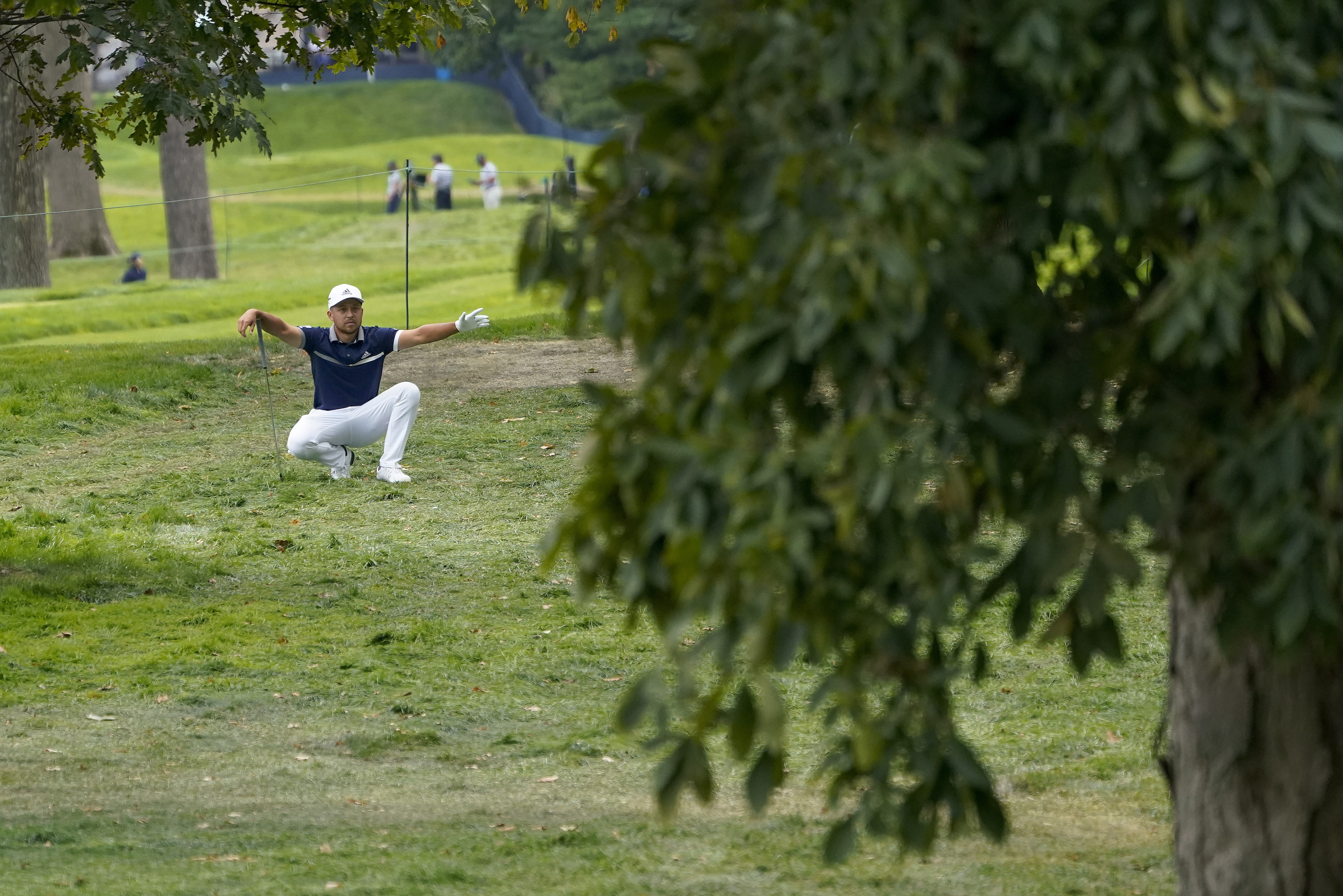 Xander Schauffele, of the United States, gestures to his caddie before hitting out of the rough on the 13th hole during the first round of the US Open Golf Championship, Thursday, Sept. 17, 2020, in Mamaroneck, N.Y. (AP Photo/Charles Krupa)