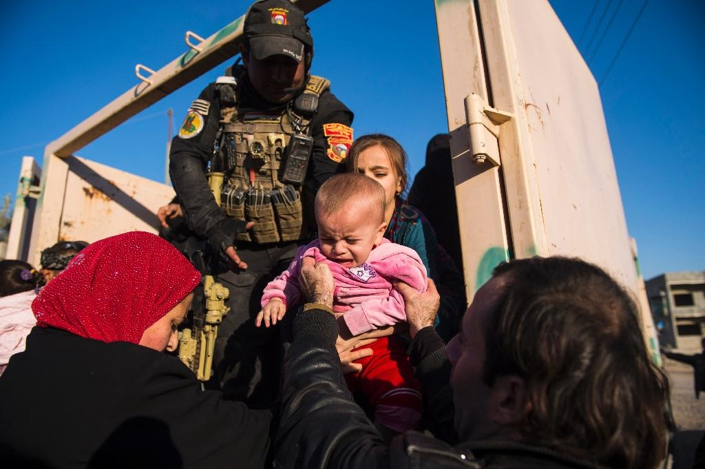 An Iraqi soldier helps people, fleeing the fighting against the Islamic State group, in the Samah neighbourhood of Mosul on November 18, 2016 (AFP Photo/Odd Andersen)