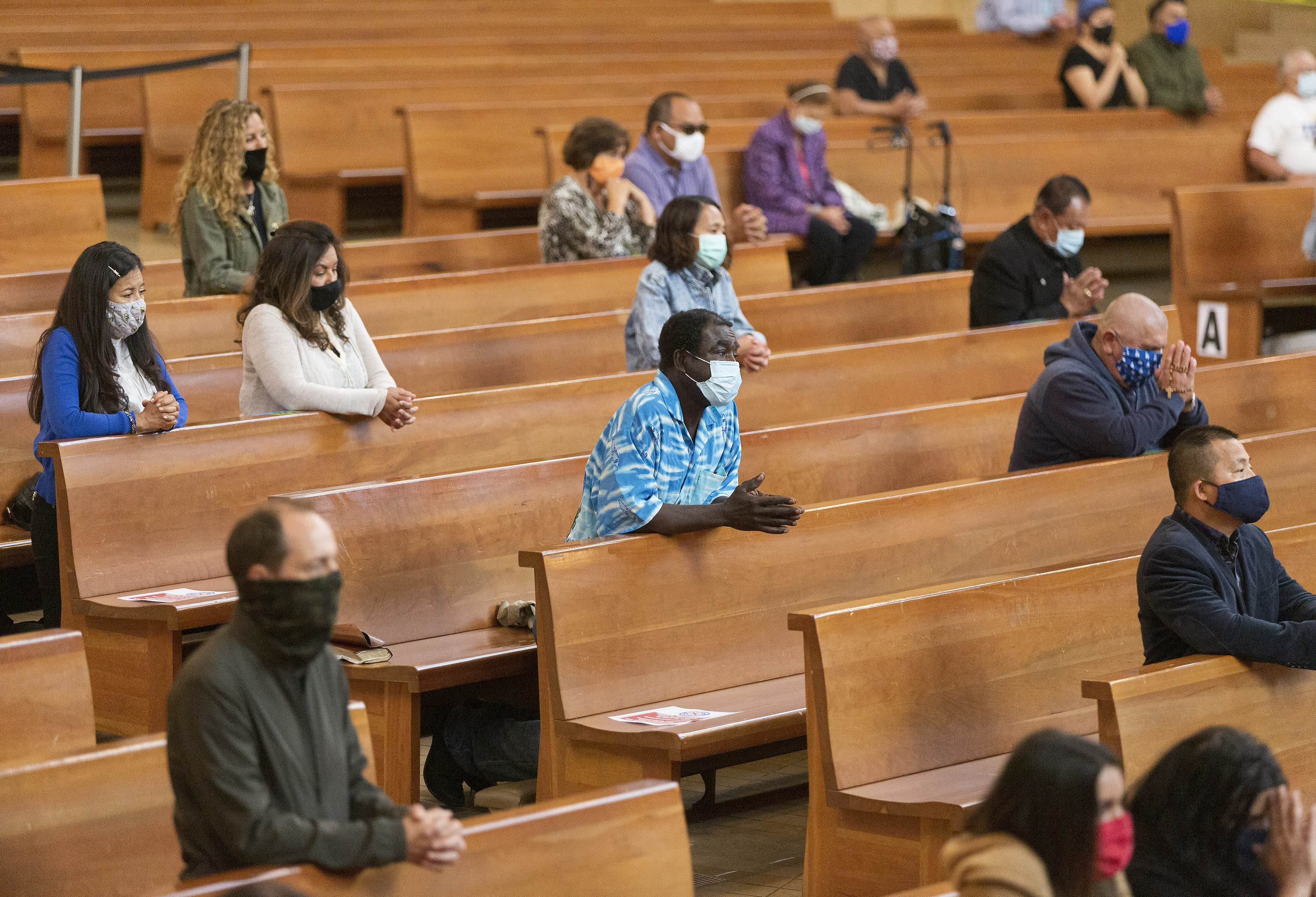 FILE - Congregants kneel and observe social distancing while listening to Los Angeles Archbishop Jose H. Gomez celebrate Mass at Cathedral of Our Lady of the Angels in downtown Los Angeles, Sunday, June 7, 2020. A religious freedom law firm with ties to President Donald Trump says it will sue California over its recent ban on singing or chanting in the church to slow the spread of the coronavirus. (AP Photo/Damian Dovarganes, File)