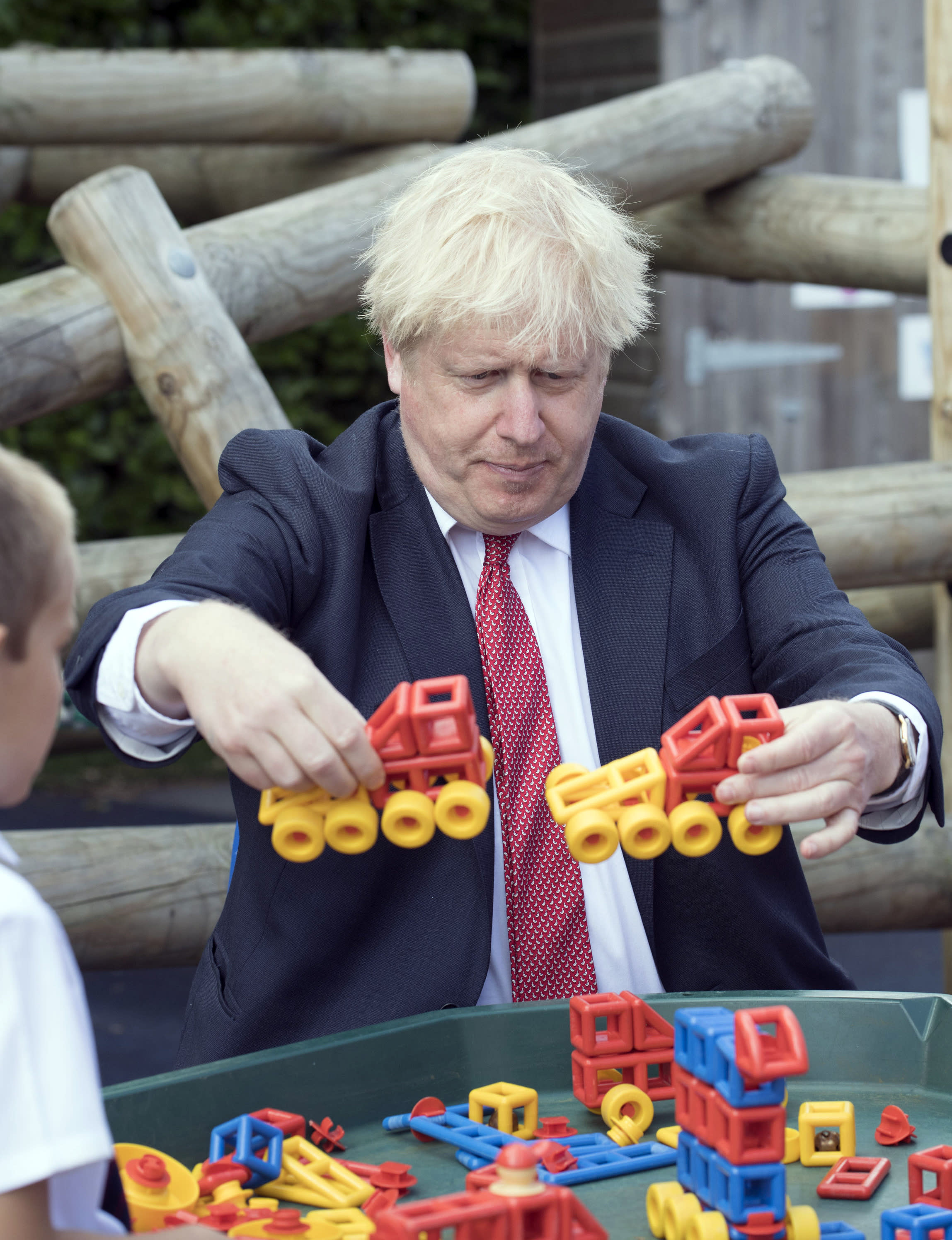 """FILE - In this July 20, 2020, file photo, Britain's Prime Minister Boris Johnson visits The Discovery School in West Malling, England. Britain's prime minister is asking parents to set aside their fears and send their children back to school next month when the nation's schools fully reopen for the first time since the coronavirus pandemic shut then down more than five months ago. Johnson said it was the government's """"moral duty'' to reopen the schools as he stressed that authorities now know more about COVID-19 than they did when the country went into lockdown on March 23. (Jeremy Selwyn/Evening Standard via AP, Pool, File)"""