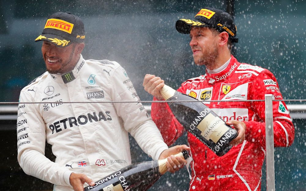 Lewis Hamilton is sprayed champagne by Sebastian Vettel on the podium after winning the Chinese Formula One Grand Prix - AP
