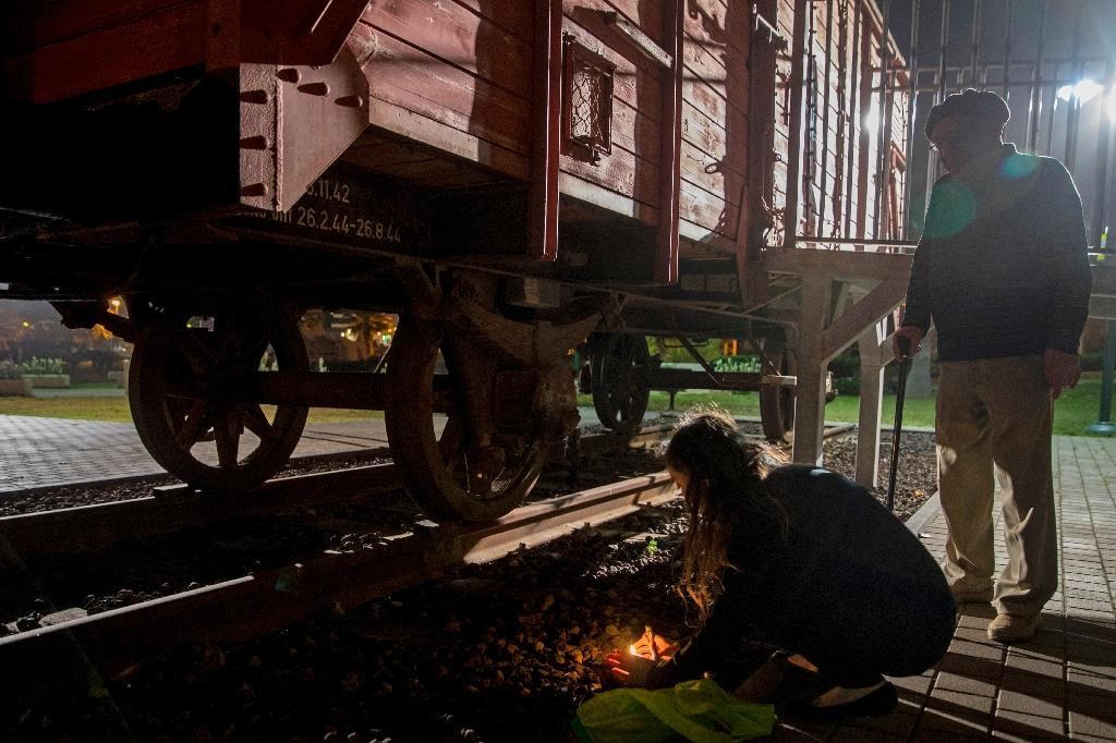 Chen and her grandfather Avraham, 85, a Holocaust survivor, light candles next to a train wagon used to transport Jews to concentration camps, in Netanya on April 23, 2017