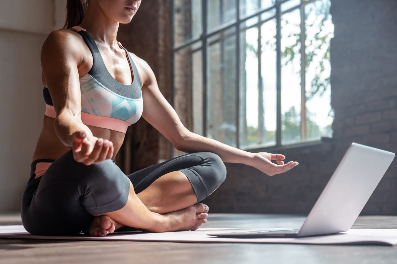Closeup young sporty fit slim woman coach do practice video online training hatha yoga instructor modern laptop meditate Sukhasana posture relax breathe easy seat pose gym healthy lifestyle concept
