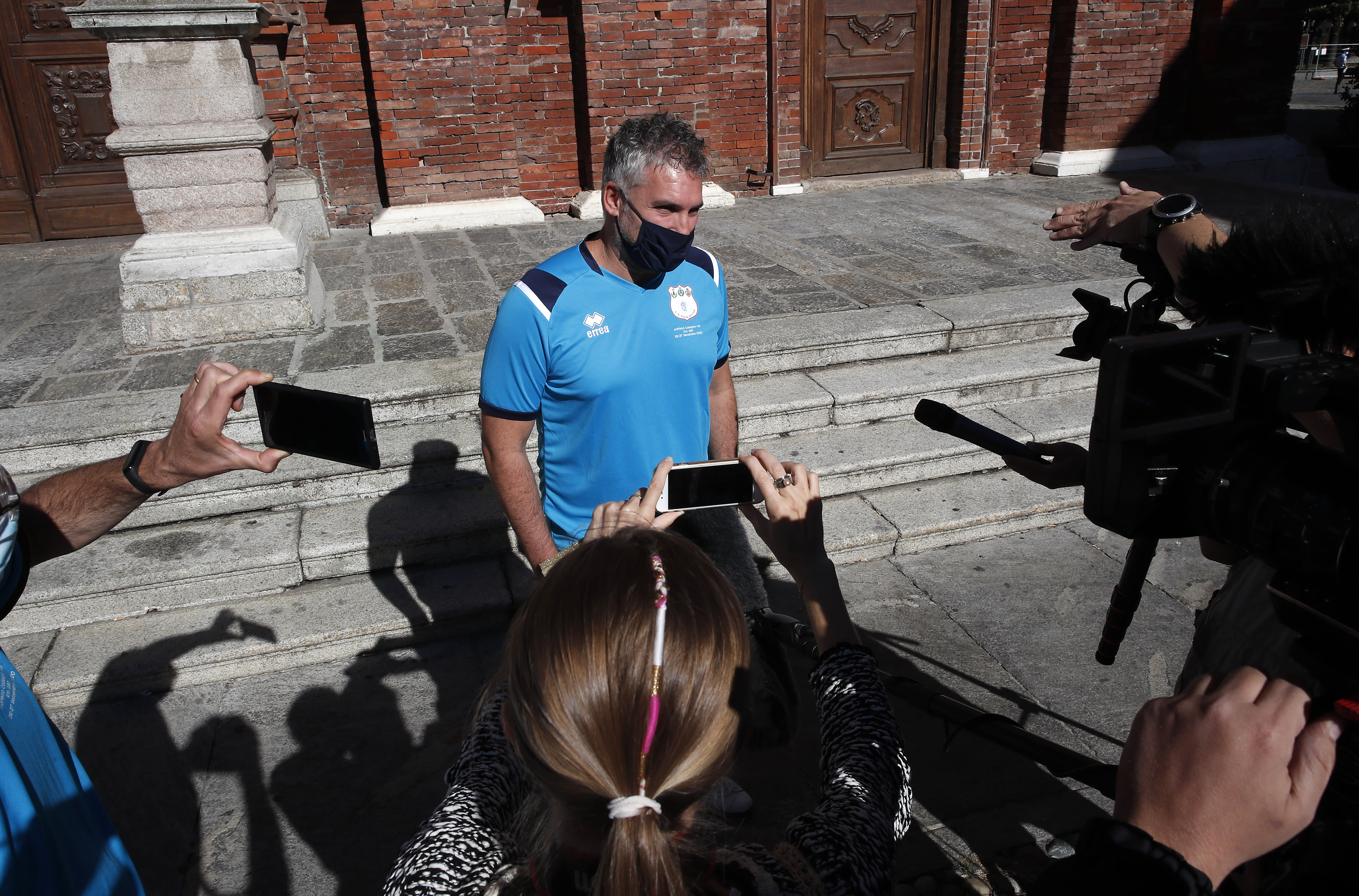 Mattia Maestri answers reporters' questions prior to the start of a 180-kilometer relay race, in Codogno, Italy, Saturday, Sept. 26, 2020. Italy's coronavirus Patient No. 1, whose case confirmed one of the world's deadliest outbreaks was underway, is taking part in a 180-kilometer relay race as a sign of hope for COVID victims after he himself recovered from weeks in intensive care. Mattia Maestri, a 38-year-old Unilever manager, was suited up Saturday for the start of the two-day race between Italy's first two virus hotspots. It began in Codogno, where Maestri tested positive Feb. 21, and was ending Sunday in Vo'Euganeo, where Italy's first official COVID death was recorded the same day. (AP Photo/Antonio Calanni)
