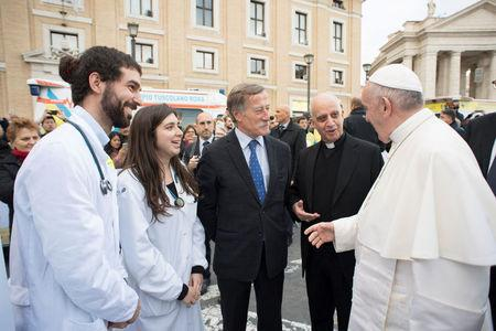 Pope Francis talks with medical personnel as he visits a first aid camp set up on the occasion of the World Day of the Poor in front of Saint Peter's square in Rome, Italy November 16, 2017. Osservatore Romano/Handout via Reuters