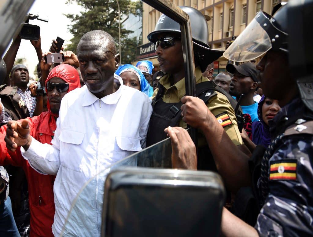 Ugandan anti-riot police arrest opposition leader Kizza Besigye on a busy Kampala street on February 15, 2016 (AFP Photo/Isaac Kasamani)