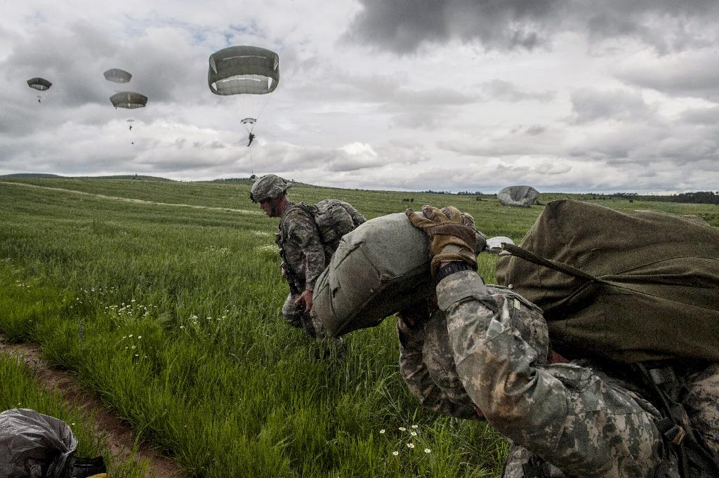 US paratroopers, part of the NATO-led peacekeeping mission in Kosovo (KFOR) jump with parachute during a military drill near the village of Ramjan on May 27, 2015