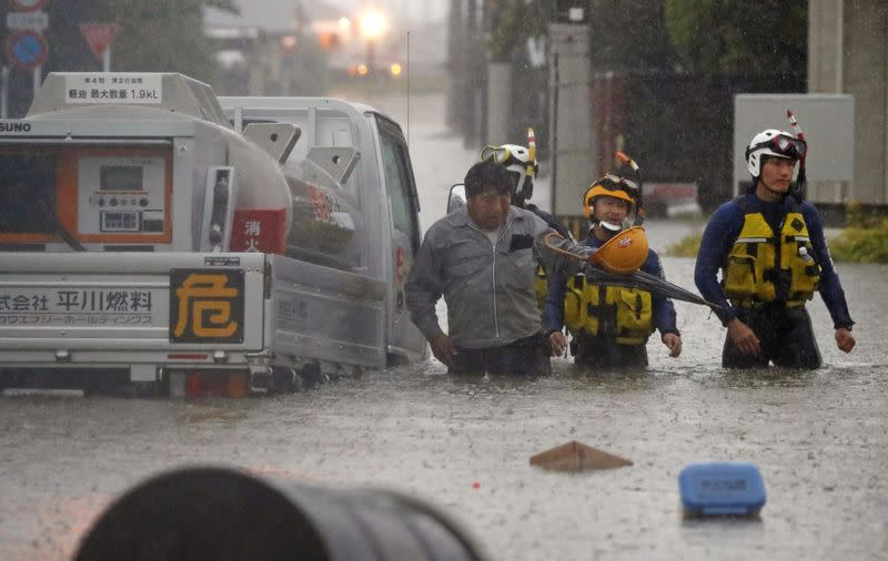 A man is rescued by police officers after his car became stuck on a flooded road caused by torrential rain in Omuta