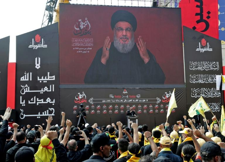 Supporters of the Lebanese Shiite Hezbollah movement react to a speech by their leader Hassan Nasrallah, transmitted or a giant screen (AFP Photo/ANWAR AMRO)