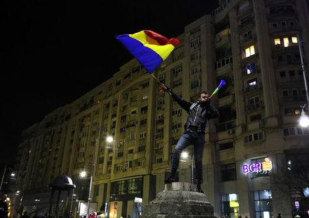 FILE PHOTO: A protester waves Romanian flag during a demonstration in Bucharest, Romania, February 3, 2017. REUTERS/Stoyan Nenov/File Photo